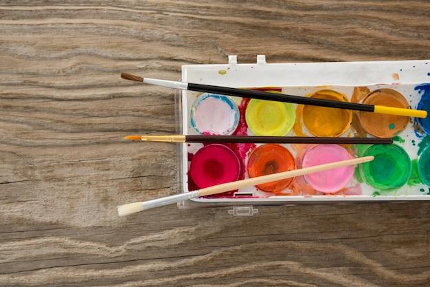Pinceles y paleta sobre superficie de madera