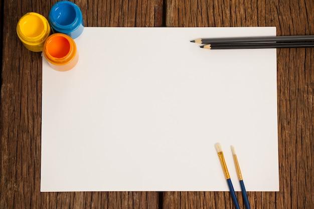 Pinceles, pinturas de acuarela, lápices de colores y papel blanco contra la superficie blanca