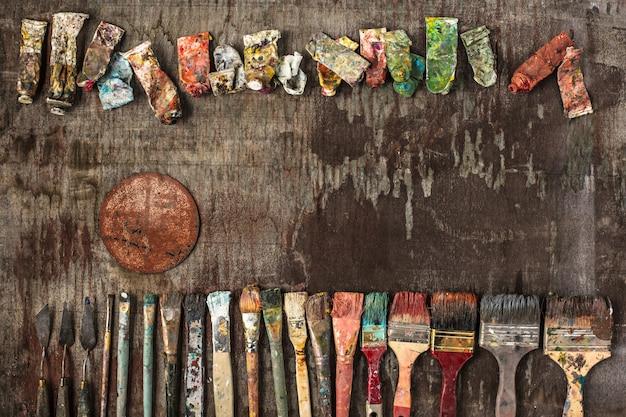 Pinceles y tubos de pinturas al óleo sobre madera.