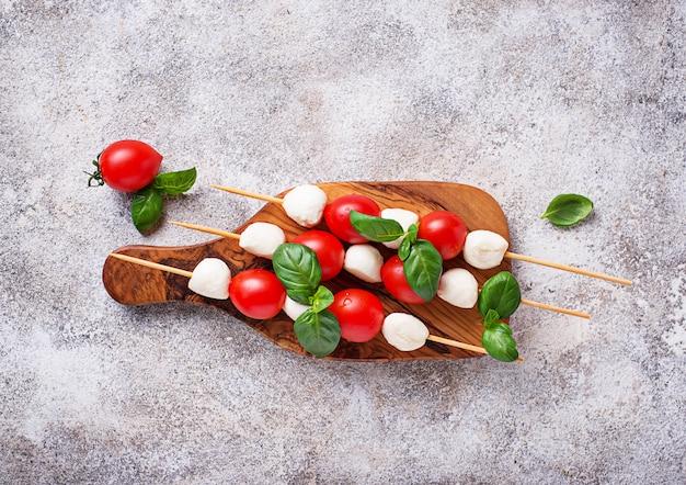 Pinchos de caprese con mozzarella, tomate y albahaca.