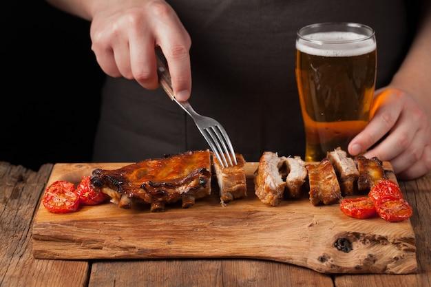 Pinchos de cocinero de hombre con un tenedor listo para comer costillas de cerdo.