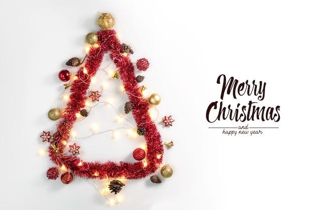Pino de navidad y adornos sobre superficie blanca