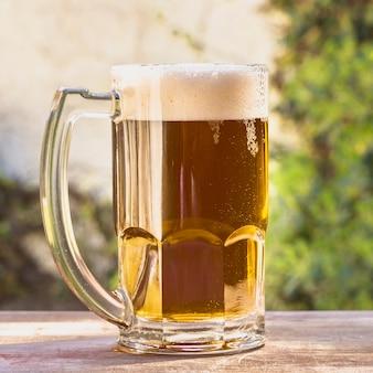 Pinta de ángulo bajo con espuma de cerveza en la mesa