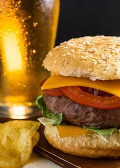 Pinta de cerveza con hamburguesa con queso y patatas fritas