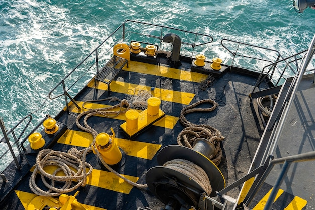 Pintado de amarillo y negro en barco con la cubierta del ferry junto con una gruesa cuerda de amarre y agua de mar, tailandia