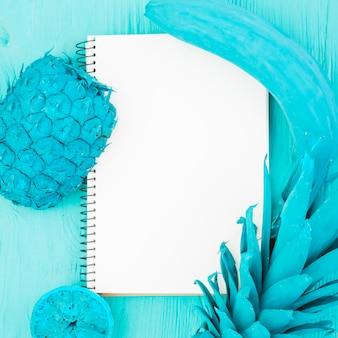 Pintado de frutas tropicales azules y cuaderno blanco.