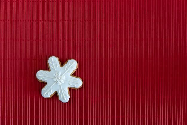 Pintado a mano navidad pan de jengibre copo de nieve blanca sobre un fondo rojo corrugado. concepto de tarjeta vista superior. endecha plana.