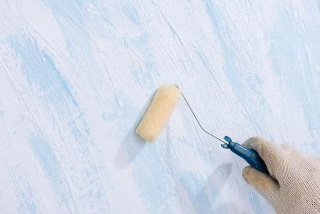 Pintar en la pared de la superficie de madera con el cepillo giratorio