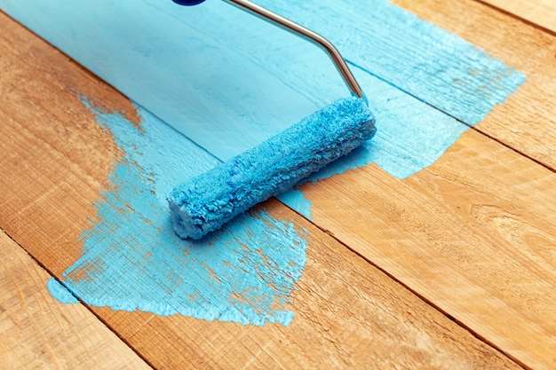 Pintar con el rodillo de pintura pintura de color azul en la bandeja de pintura verde en el fondo de madera de bricolaje
