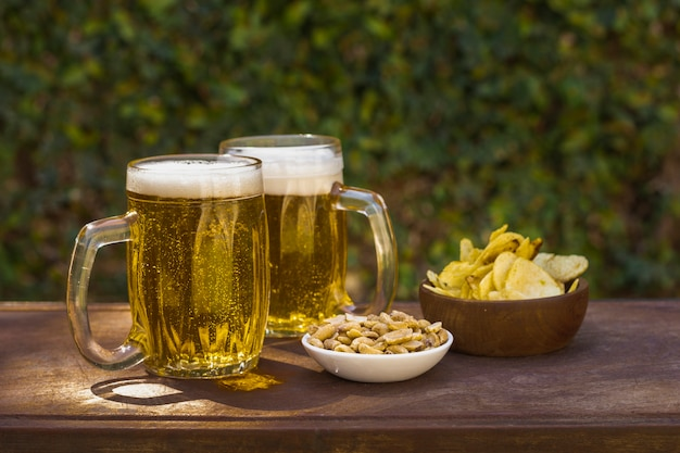 Pintas de alto ángulo con cerveza y aperitivos en la mesa