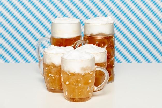 Pintas de cerveza rubia en mesa blanca