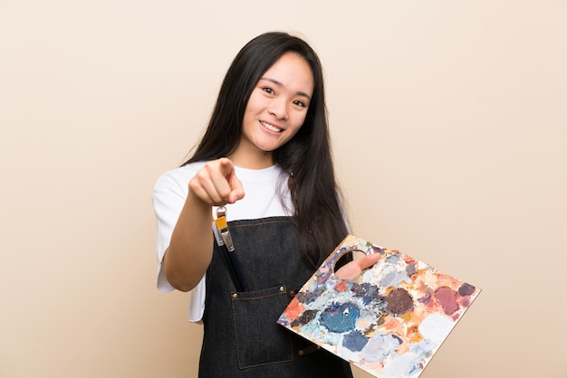 Pintor adolescente chica asiática te señala con una expresión de confianza