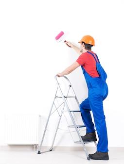 Pintor artesano se encuentra en las escaleras con rodillo, retrato completo en blanco
