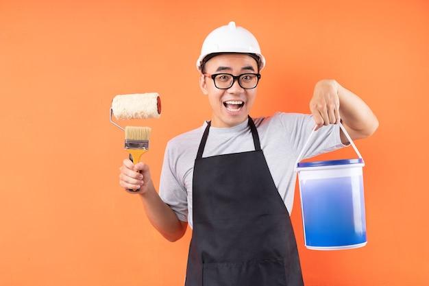 Pintor asiático con pincel posando en la pared naranja
