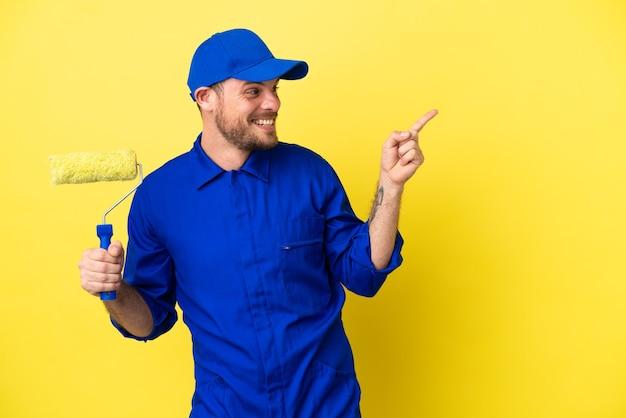 Pintor brasileño aislado sobre fondo amarillo apuntando con el dedo hacia un lado y presentando un producto