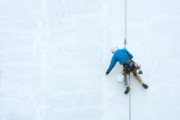 Pintor colgado en nuevo edificio blanco