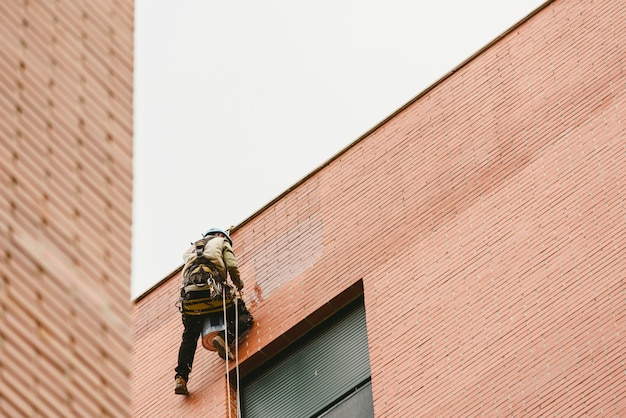 Pintor escalador suspendido de cuerdas y arneses pinta el exterior de un edificio de apartamentos