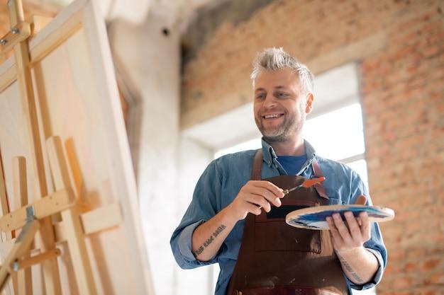 Pintor feliz y exitoso con paleta mirando el caballete mientras está de pie frente a la pintura en el estudio