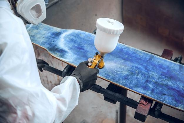 Pintor maestro en una fábrica - pintura industrial de madera con pistola.