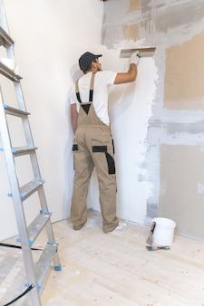 Pintor masculino con una espátula en sus manos hace reparaciones en casa