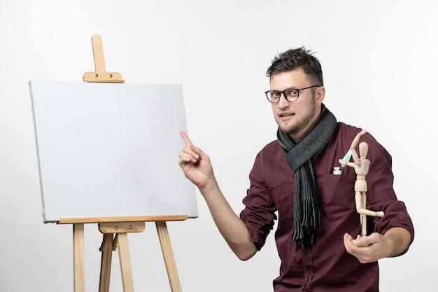 Pintor masculino de vista frontal junto con caballete sosteniendo una figura humana en la pared blanca