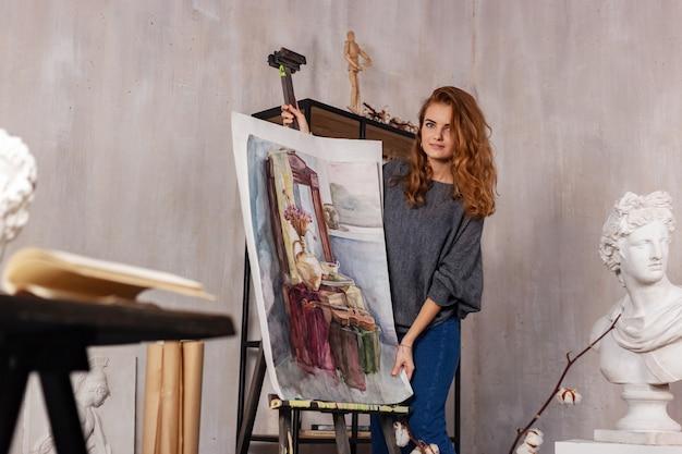 Pintor de la mujer que sostiene un cepillo y una paleta con las pinturas de aceite en su mano, dibujando.