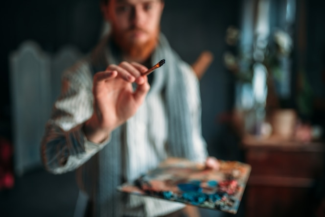 pintor con paleta y pincel en mano