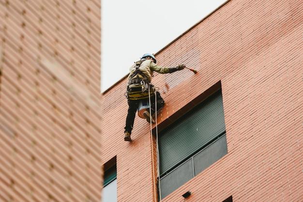 Pintor posado colgado en las paredes de un edificio con cuerdas.