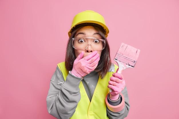 Pintor profesional ocupado cubre la boca con la mano