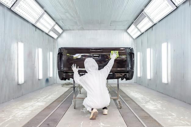 Pintor reparador de automóviles en ropa de trabajo protectora y respirador pintando carrocería en cámara de pintura