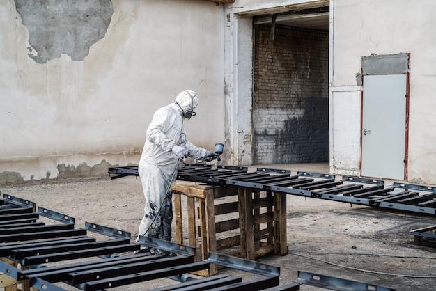 Pintor con ropa protectora pinta productos metálicos al aire libre con pistola pulverizadora