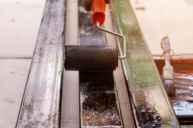 El pintor usa guantes de tela, usando un rodillo de pintura negro en la barra de acero.