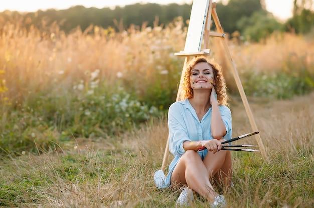 Pintora bastante talentosa pintando en caballete, haciendo bocetos coloridos, creando un paisaje marino. hermosa artista femenina pintando con pinturas de acuarela. concepto de creatividad e imaginación.