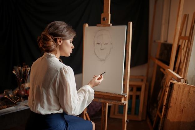 Pintora en estudio, dibujo a lápiz sobre caballete. pintura creativa, retrato de dibujo de mujer, interior del taller en el fondo