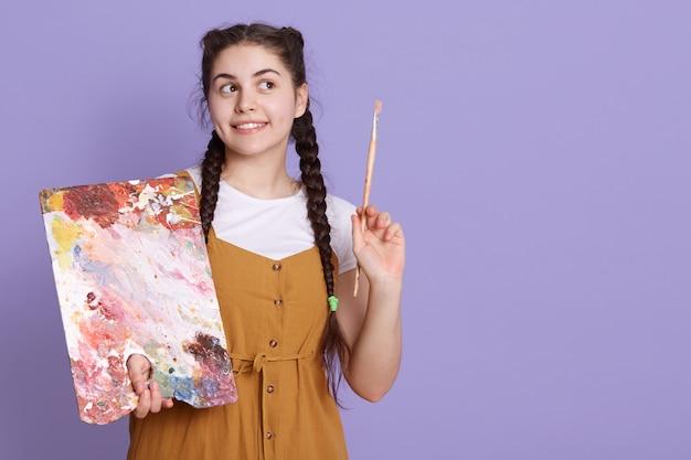 La pintora feliz joven piensa en un nuevo proyecto, tiene una expresión facial pensativa, mirando sonriendo a un lado, posando aislada sobre la pared lila. copie el espacio.