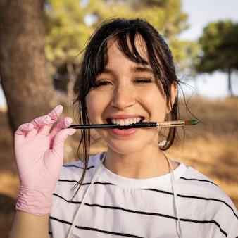 Pintora sonriente sosteniendo cepillo entre sus dientes