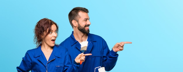 Pintores apuntando con el dedo hacia un lado y presentando un producto mientras sonríen.