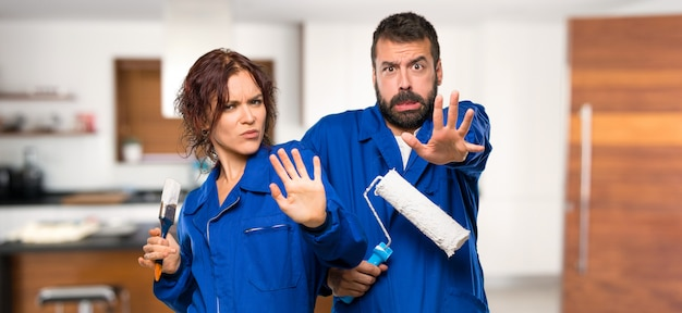Los pintores están un poco nerviosos y asustados estirando las manos hacia el frente de la casa.