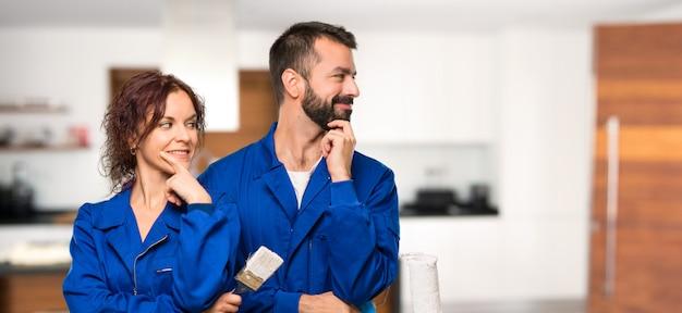 Pintores mirando al costado con la mano en la barbilla en casa.