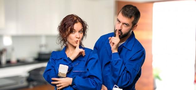 Pintores mostrando un signo de boca cerrada y gesto de silencio en casa.