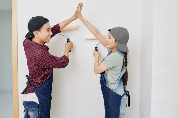 Pintores de pared dando cinco