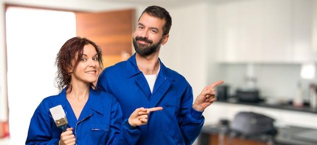 Pintores que apuntan hacia un lado con un dedo para presentar un producto en casa.