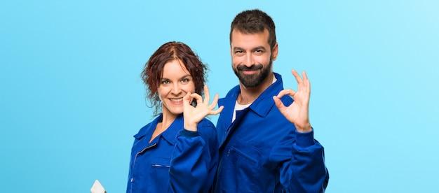 Pintores que muestran un signo aceptable con los dedos en el fondo de colores