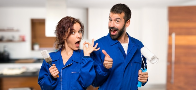 Pintores que muestran un signo de ok y que hacen un gesto con el pulgar arriba con la otra mano en la casa