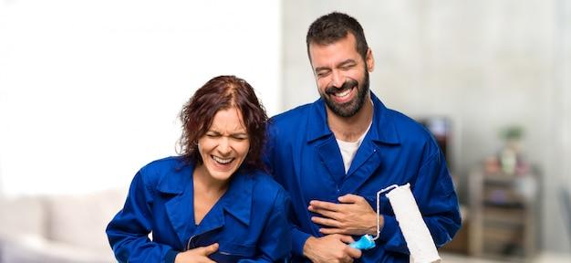 Pintores sonriendo mucho mientras se ponen las manos en el pecho en casa