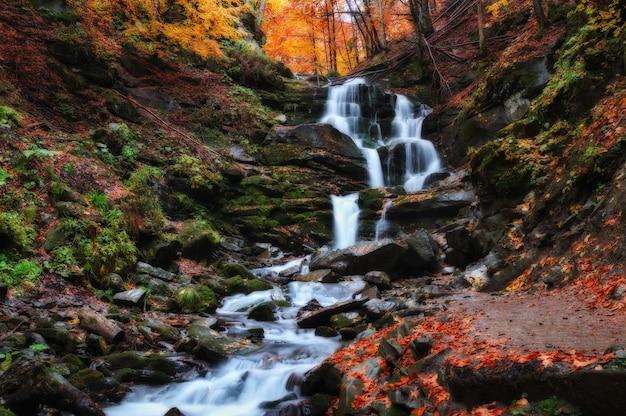 Pintoresca cascada en el bosque de otoño