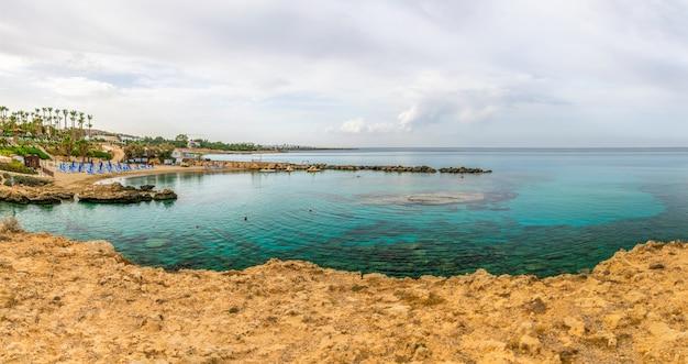 Una pintoresca playa con aguas cristalinas se encuentra a orillas del mar mediterráneo.