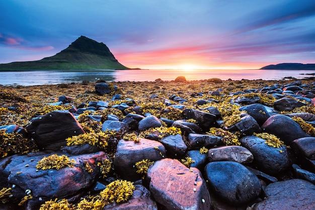 La pintoresca puesta de sol sobre paisajes y cascadas. montaña kirkjufell, islandia