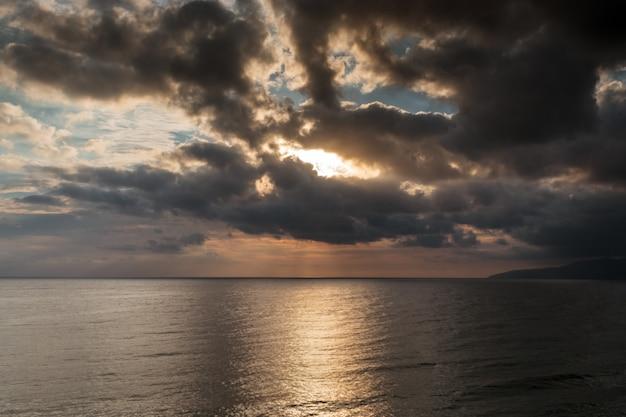 El pintoresco amanecer sobre el mar mediterráneo. clima nublado, nubes oscuras cubren el sol naciente