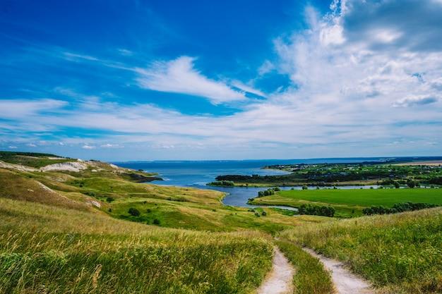 Pintoresco paisaje con colinas y campos de flores y cielo azul
